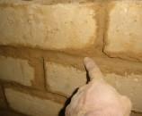 האצבע מסדרת את הטיט ליצירת המרקם הרצוי, כשהטיט שקוע מעט ומבליט את הלבנים החוצה