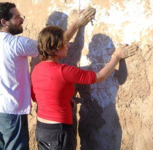 מריחה של טיח בוץ שכבה ראשונה על קיר צבוע במשחת קמח.