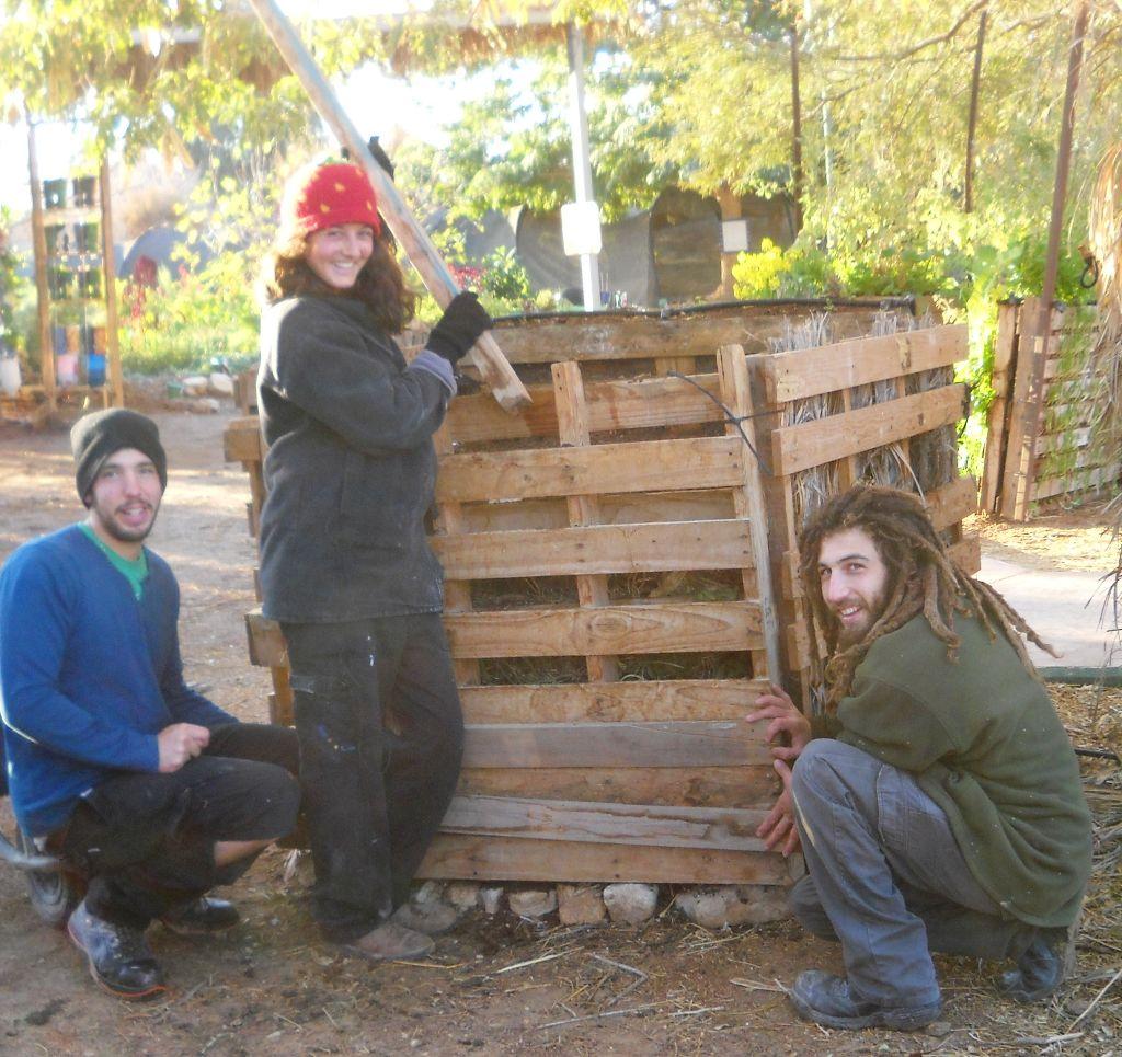 חברים מחזיקים קורות עץ בפתחי המשטח בזמן הידוק האדמה על מנת שלא תיפול החוצה
