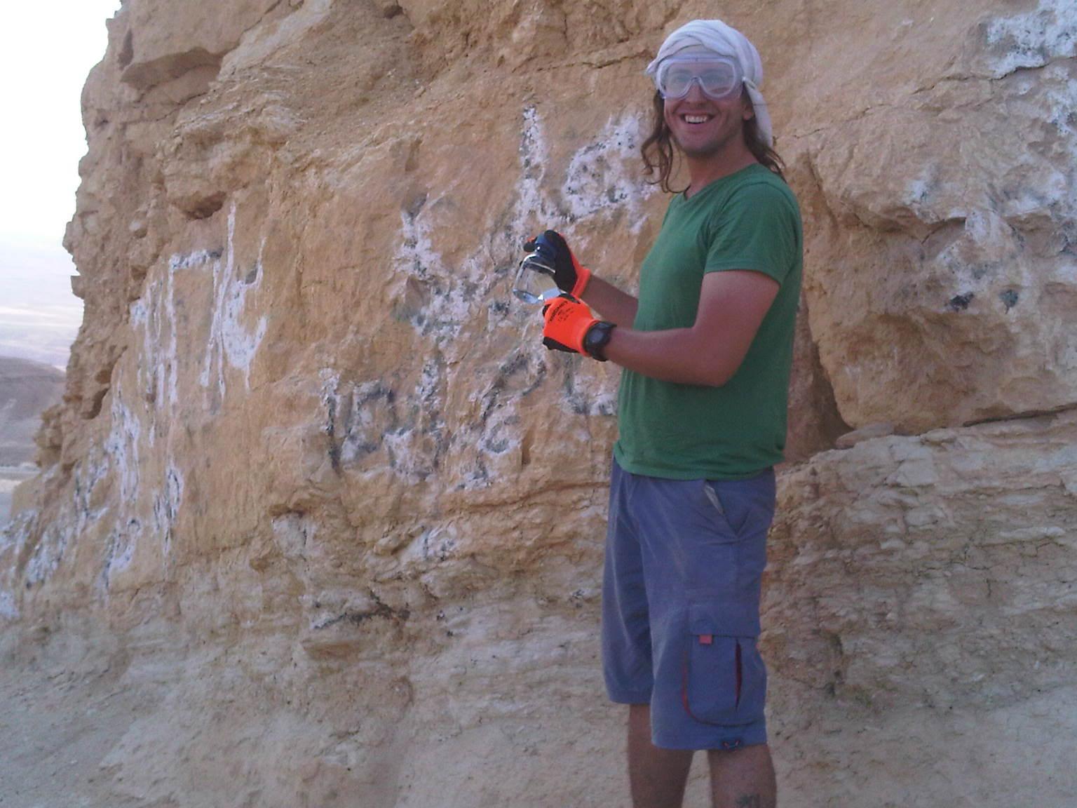 שימוש בחומרים מסוכנים סימו לב לאורך הקיר האינסופי וכמות הגרפיטי שעליו - מחיקת גרפיטי במדבר