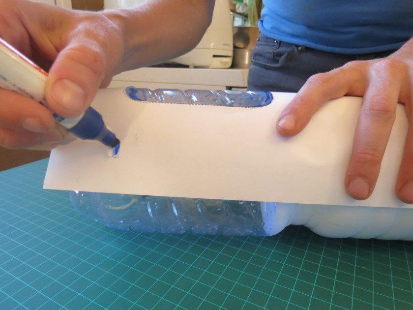 הניחו את דפי השבלונה מסביב לבקבוקים כאשר הדף בקו אחד עם בסיס הבקבוק. סמנו נקודות לחיתוך עם טוש בכל הבקבוקים.