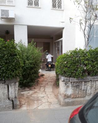 שליח של עיתון נכנס רכוב על אופנועו לתוך חצר עד תיבות הדואר