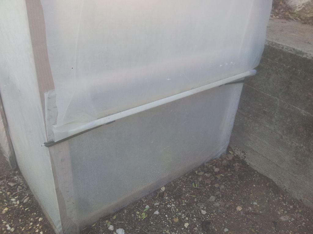 חלון סגור: הפלסטיק מגולגל על מוט עץ שמהודק בשתי קצוותיו לברגים בשלד החממה כדי למתוח את יריעת הפלסטיק