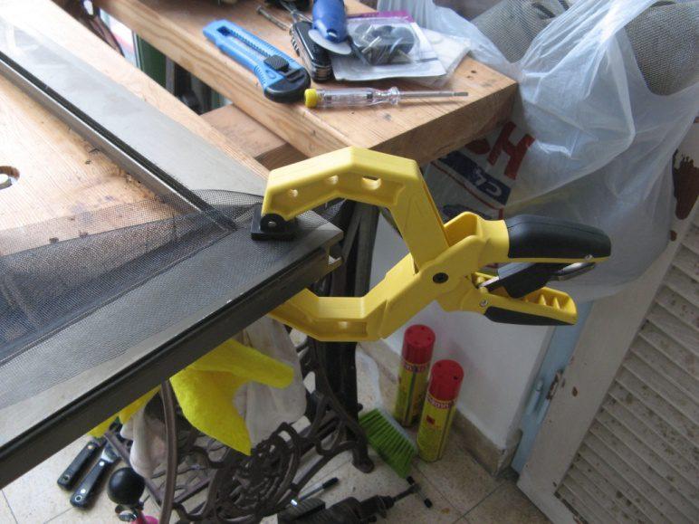 קיבוע פס הגומי באחת הפינות, יישור הרשת ומתיחתה. לנגר חובב יש כלים להחזיק את הפינה במקום