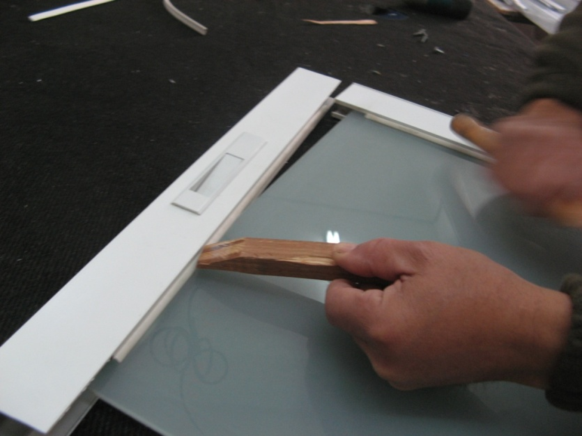 פירוק החלון בעזרת קרש עץ ופטיש גומי, לאחר הוצאת הברגים: