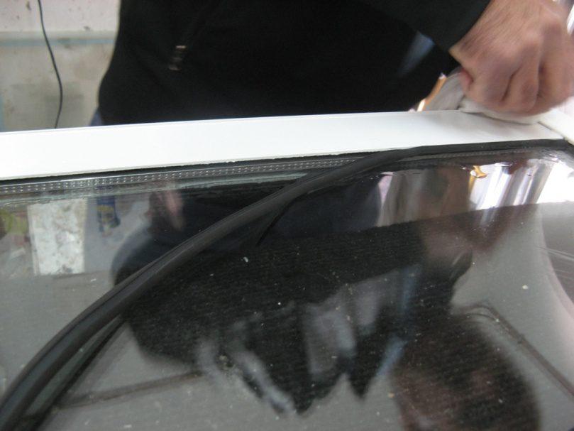 לאחר הכנסת הזיגוג וסגירת הברגים, הגיע תור דחיסת פסי גומי סביב הזכוכית, תוך הרטבה ושימוש בכוח