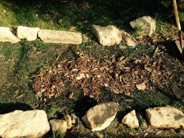 רסק עץ על רשת פלסטיק ליצירת שביל בגינה.