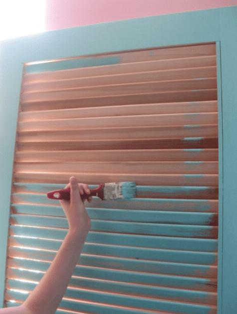 בתמונה הבאה נראית בתי צובעת את דלת התריס ביציאה מאותו חדר למרפסת