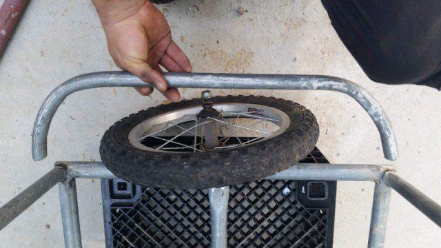 הגלגל עומד בתוך המקום היעודי לו - עם הצינור המכופף מוחזק ביד להמחשה