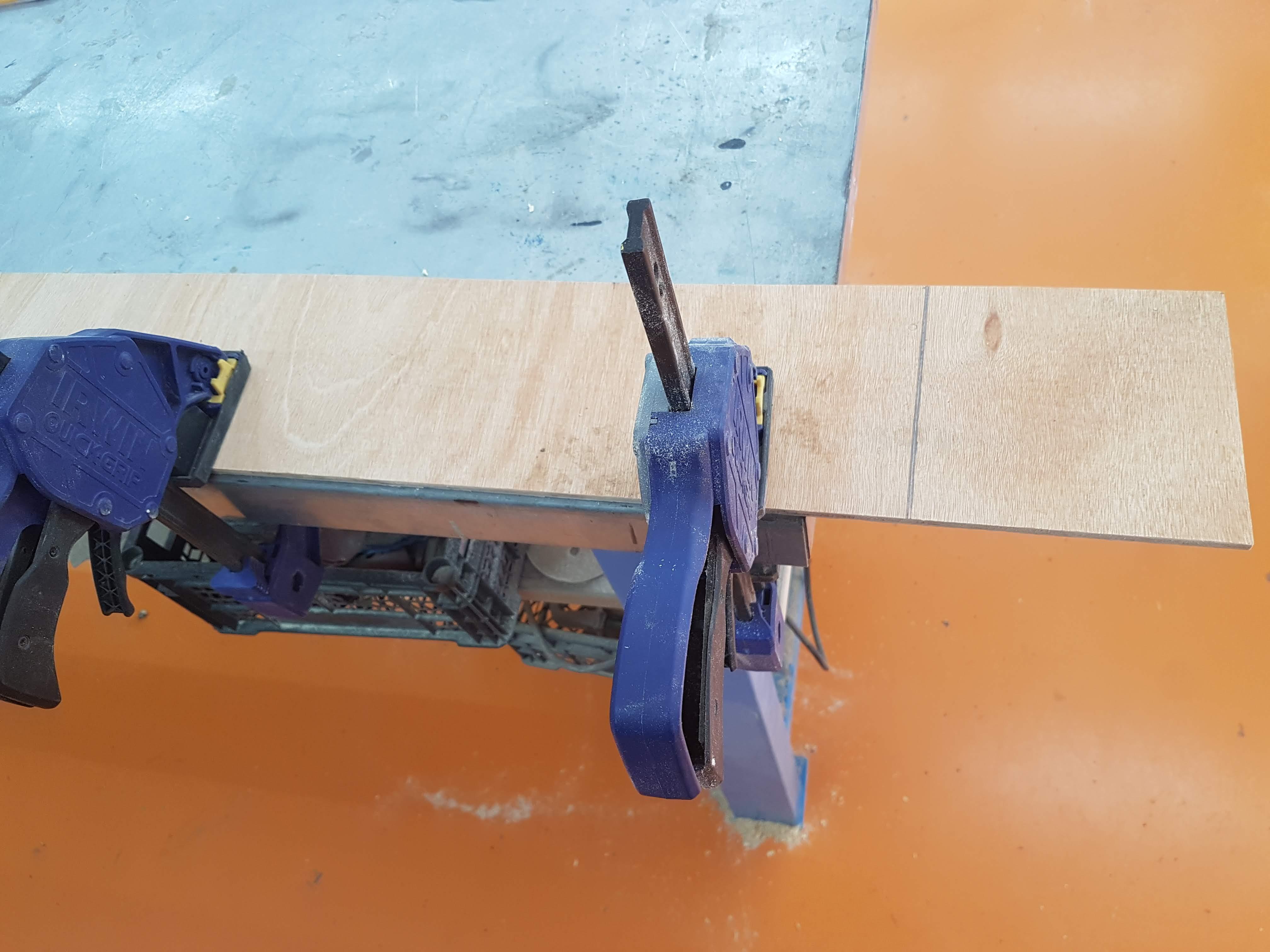 אחיזה של הלוח בקצה השולחן, כשקו החיתוך במרחק של 3-4 ס: